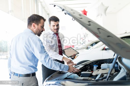 136591850 istock photo Dealer And Customer Discussing Over Car Engine 1127882072