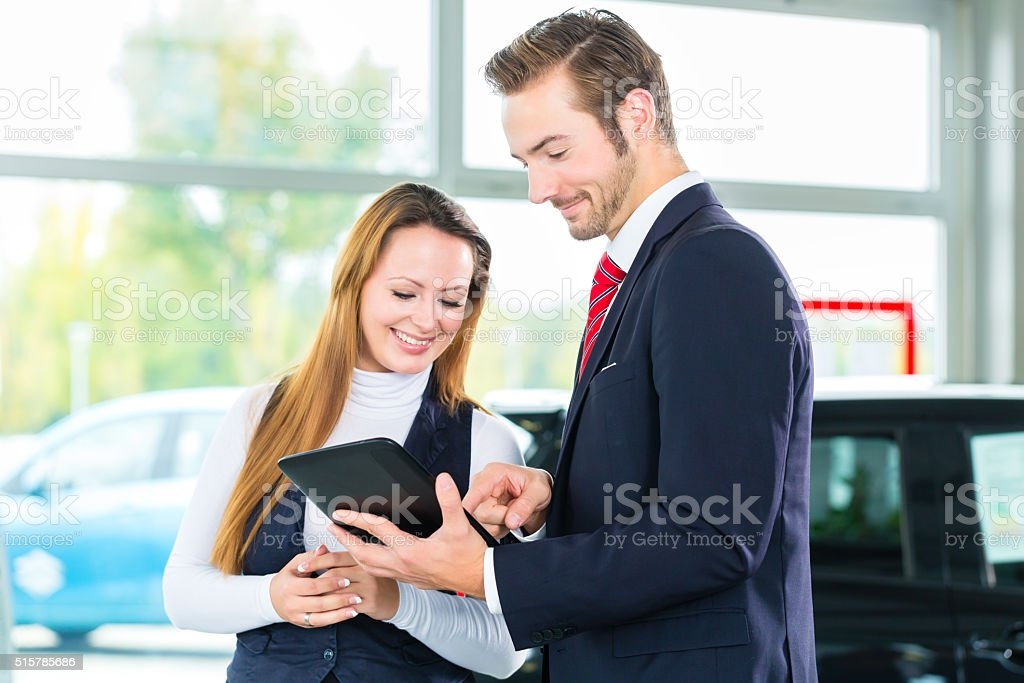 Dealer, female client and auto in car dealership stock photo