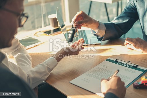 936987338 istock photo dealer salesman giving car key to owner. client signing insurance document or rental car lease form 1192579289