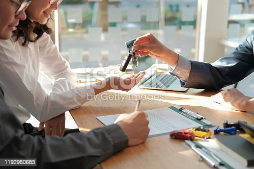 936987338 istock photo dealer salesman giving car key to owner. client signing insurance document or rental car lease form 1192980683