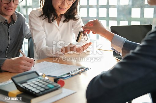 936987338 istock photo dealer salesman giving car key to owner. client signing insurance document or rental car lease form 1193199617