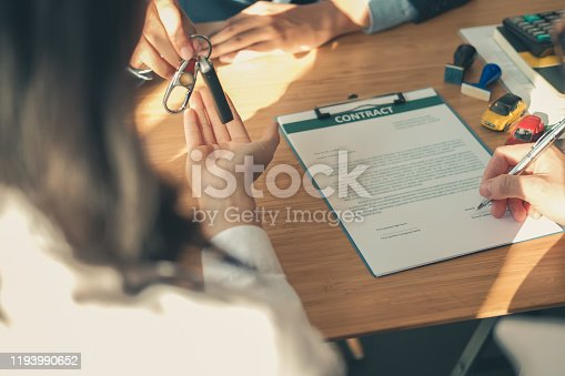 939005154 istock photo dealer salesman giving car key to owner. client signing insurance document or rental car lease form 1193990652