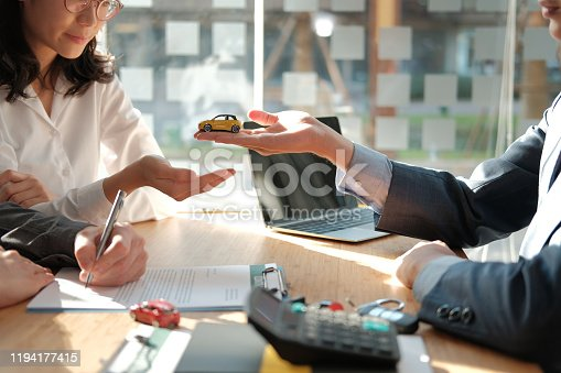 936987338 istock photo dealer salesman giving car to owner. client signing insurance document or rental car lease form 1194177415
