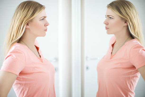 Dealing with body image issues. Young woman looking at mirror, not liking what she sees. low self esteem stock pictures, royalty-free photos & images
