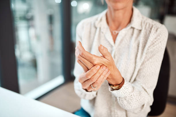 Dealing with hand pain and stiffness stock photo