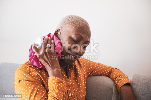 Gray haired African descent woman experiencing a headache