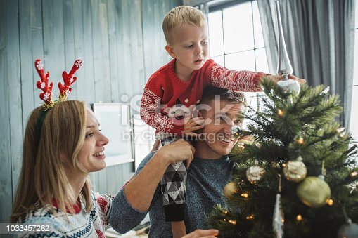 Young parents with baby boy celebrating Christmas at home and decorating christmas tree and plays around it. Home is decorated with Christmas ornaments and lights.