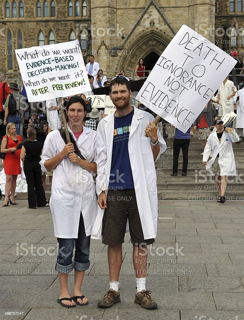 """Death of Evidence March in Ottawa, Canada """"Ottawa, Canada  - July 10, 2012:  Hundreds of Canadian scientists marched on Parliament Hill in a Death to Evidence  march to protest deep cuts and restrictions to their industry by the Conservative government."""" Apron Stock Photo"""