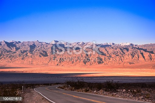 Desert road in Death Valley with mountain background of Death Valley.