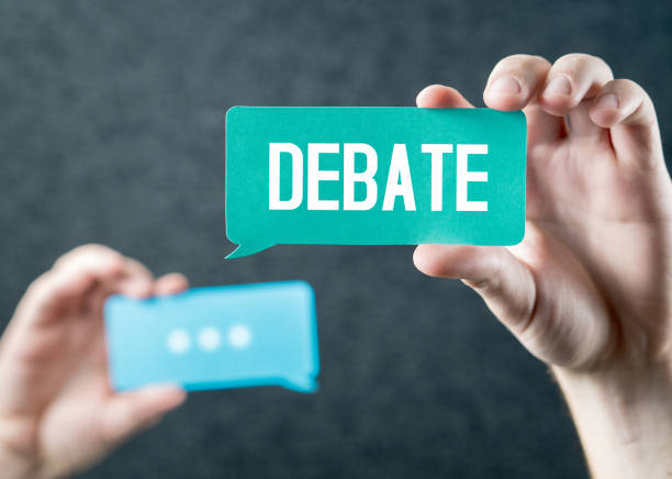 debate, argument, controversy and disputation concept. learning to be better speaker. education to improve dialog. tell opinions and thoughts in public. hands holding cardboard speech bubble. - debate стоковые фото и изображения