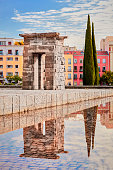 Madrid, Spain - September 29, 2020: Arch of the Temple of Debod. Reflection in the water and colorful buildings.