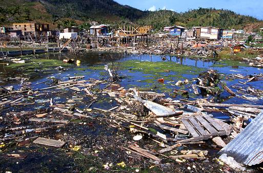 Debris remaining in pond and destruction from 1998 Hurricane Mitch in Savanna Bight village Guanaja Bay Islands Honduras