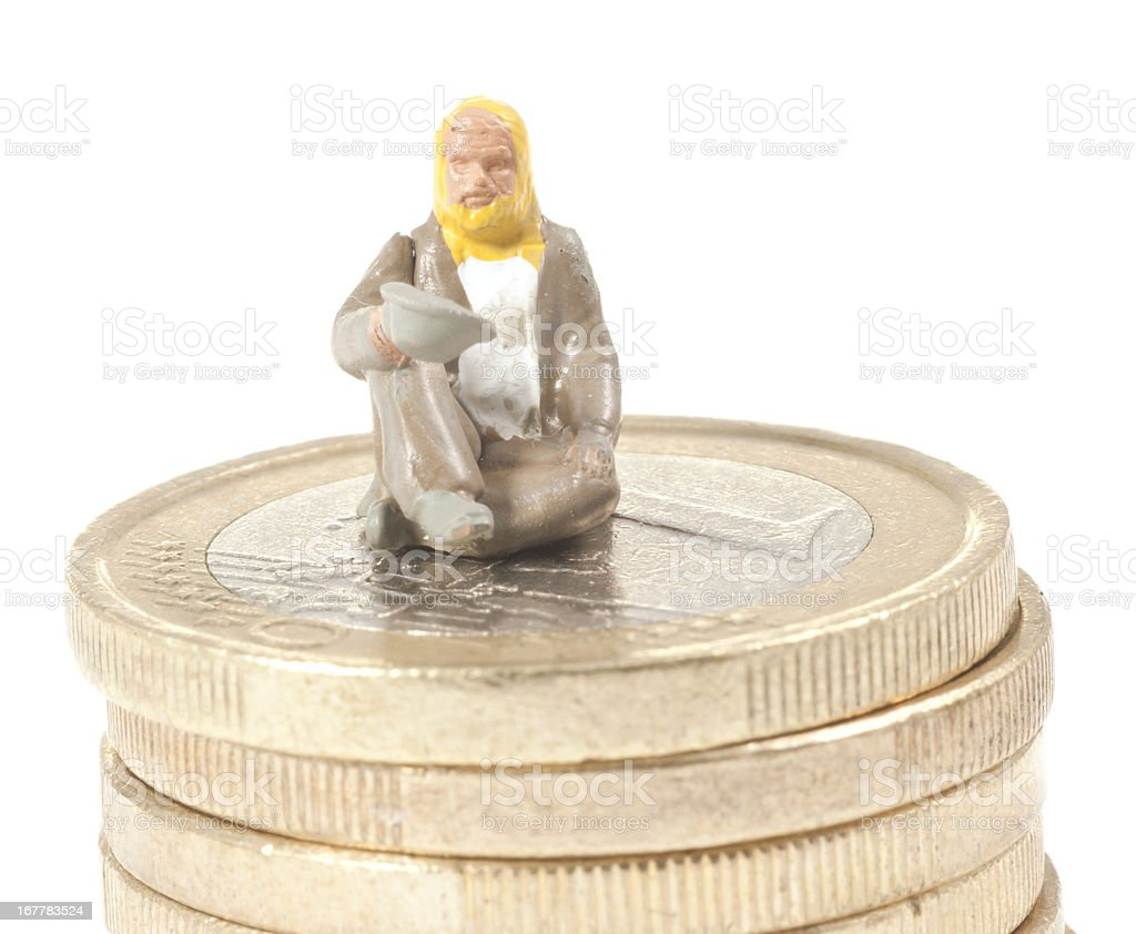 debt abstract with begger on stack of euro coins stock photo