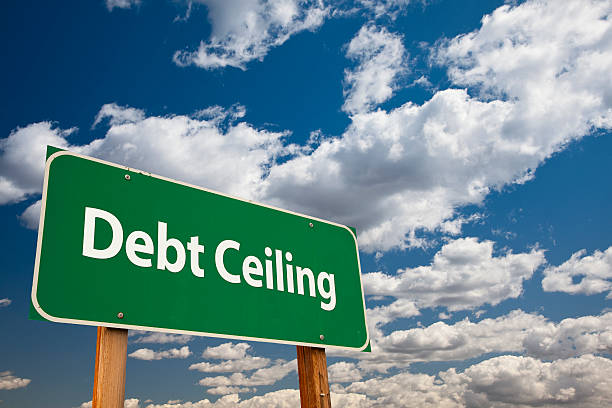 Debt Ceiling Green Road Sign Debt Ceiling Green Road Sign Over Clouds and Sky. debt ceiling stock pictures, royalty-free photos & images