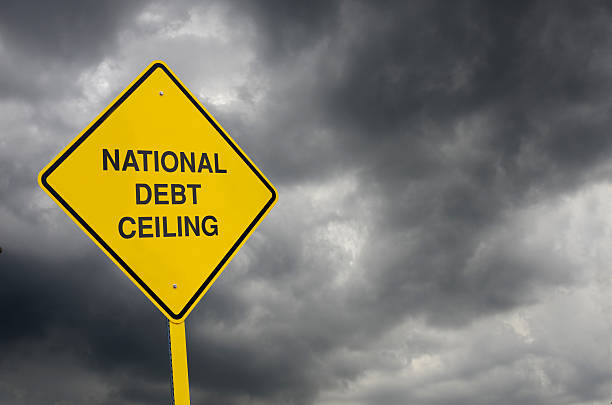"Debt Ceiling Road Sign A Caution Sign in front of storm clouds warning of the looming ""National Debt Ceiling"". debt ceiling stock pictures, royalty-free photos & images"