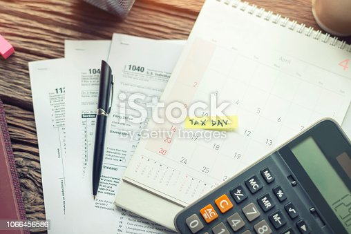 istock Debt collection and tax day with deadline calendar reminder note, U.S. tax form 1040, calculator on wooden background. Top view, Time to payment concepts. 1066456586