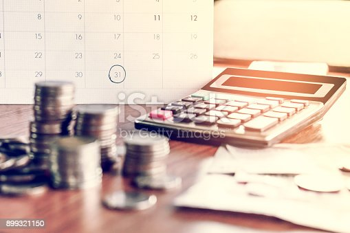 istock debt collection and tax season concept with deadline calendar remind note,coins,banks,calculator on table 899321150