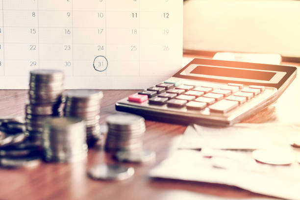 debt collection and tax season concept with deadline calendar remind note,coins,banks,calculator on table - foto stock