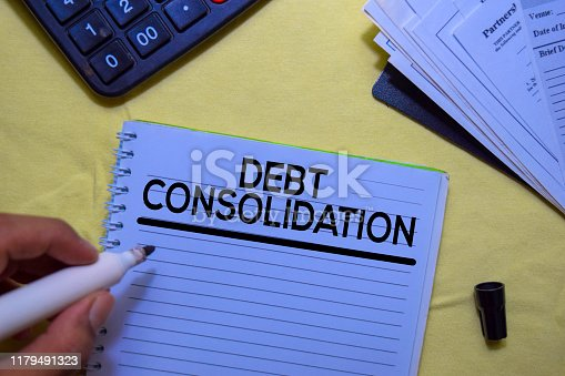 Debt Consolidation text on a book isolated on office desk.
