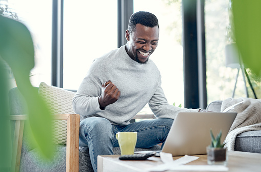 Shot of a young man celebrating while going over paperwork and using a laptop at home