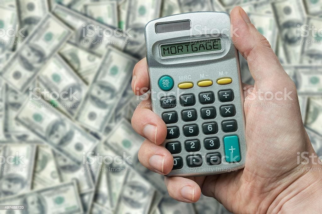 Debtor is using calculator to calculate repayments for mortgage stock photo