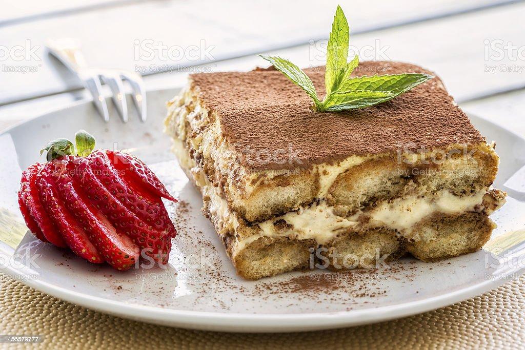 A decadent dessert of tiramisu on a plate with a strawberry stock photo