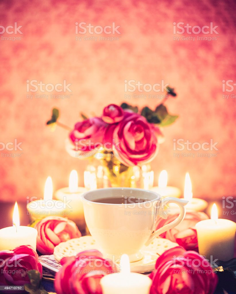 Decadent tea party with tea, roses and candlelight stock photo