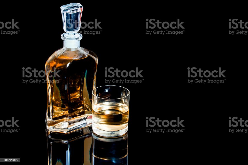 Decanter and a glass of whiskey on a black background stock photo