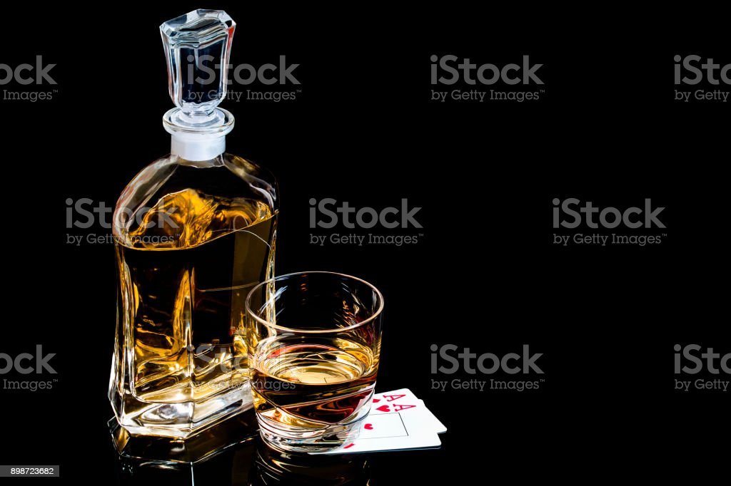 Decanter and glass of whiskey with poker cards stock photo