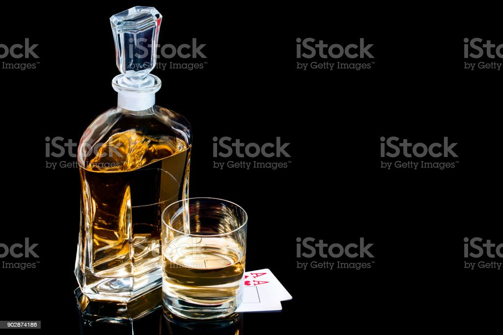 Decanter and the glass of whiskey with poker cards on the black background stock photo