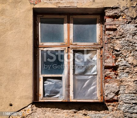 Decaying plasterwork, brickwork and a window on a building in the Old Town in Tallinn (Vanalinn), capital of Estonia, in bright sunshine. The window frame is in very bad condition and some of the panes of glass are missing, with the empty sections having been covered over with polythene.