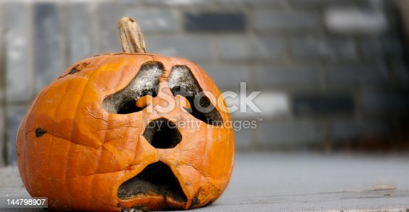 A sad decaying pumpkin waitng for the end of Halloween.