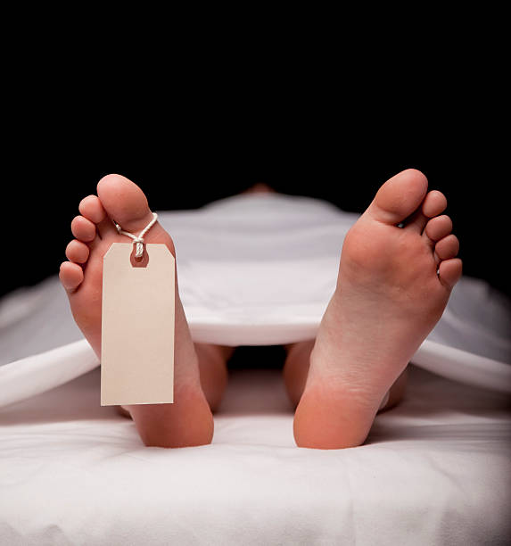 Deceased Person Laying on Table with Toe Tag Attached stock photo