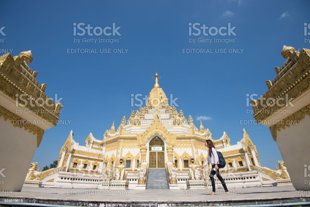 15 December 2016 Female tourist walking at Swe Taw Myat, Buddha Tooth Relic Pagoda a famous and beautiful buddhist temple in yangon , myanmar stock photo
