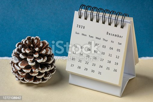 December 2020 - spiral desktop calendar against colorful handmade paper with a decorative frosty pine cone, season,  time and business concept