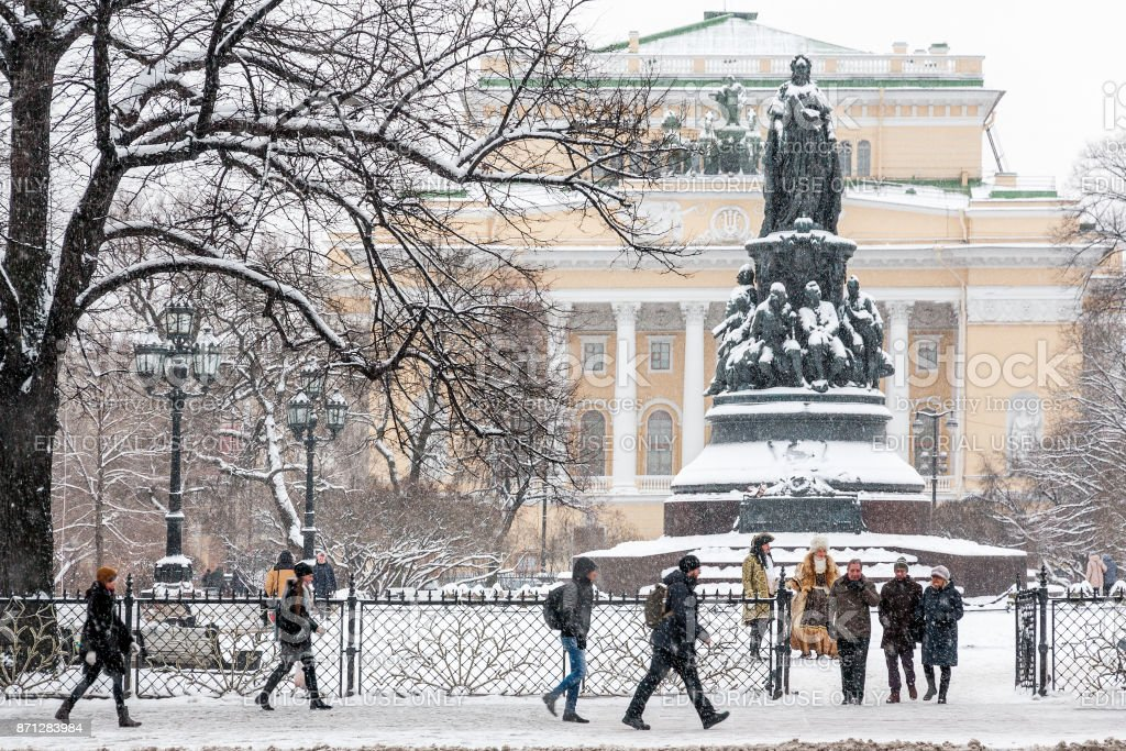 December 3rd, 2016. Historical landmark and touristic spot in Saint Petersburg, Russia: historical Alexandrinsky theater and square in front of it with monument of russian queen Catherine the Great and people walking by a winter day with snow and snowfall stock photo