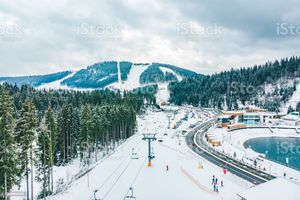 BUKOVEL, UKRAINE - December 9, 2018 - people skiing and snowboarding down by hill. winter activity stock photo