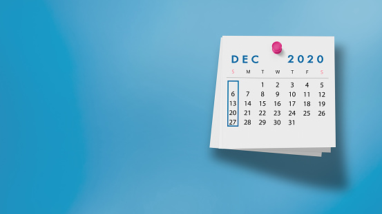 2020 December calendar on a white note paper pinned on wall against blue background. High resolution and copy space for all your crop needs.