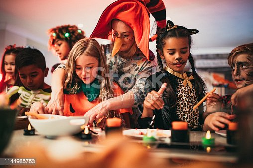 Children sitting in a line deciding which foods to eat while at a Halloween party. They are all wearing costumes and one of the children is being helped by a parent