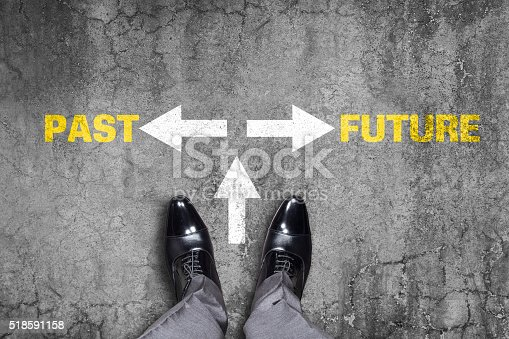 Low section view of a businessman standing by text Past or Future with arrow sign represents the concept of forecasting.