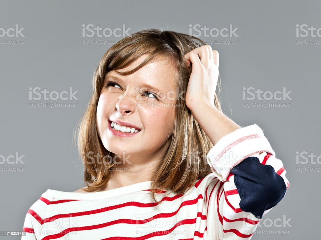 Decision Portrait of cute girl wearing striped blouse looking away with hand in hair. Studio shot. 10-11 Years Stock Photo