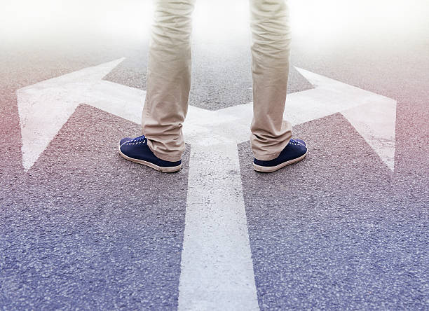 Decisions about the future Arrows painted on asphalt. Young man standing hesitating to make a decision. fork in the road stock pictures, royalty-free photos & images