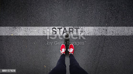 Red shoes standing next to start line painted text
