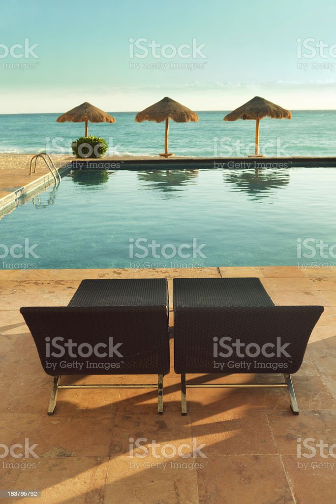 Deck Chair Pair by Swimming Pool, Palapas, and Caribbean Sea royalty-free stock photo