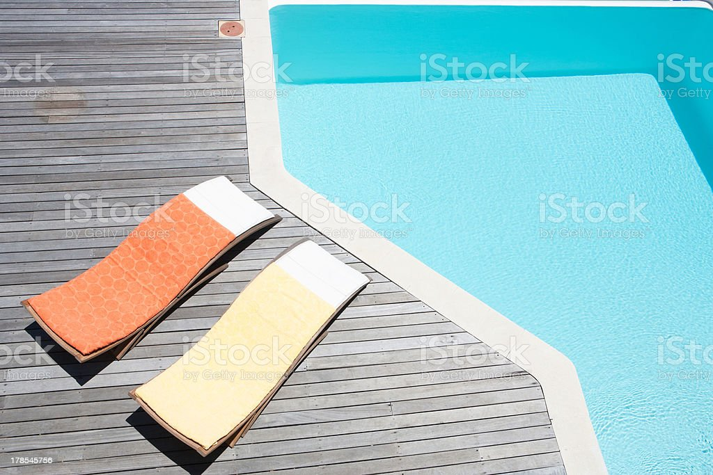 Deck chairs beside swimming pool stock photo