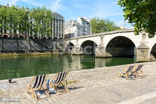 Blue and white striped deck chairs in the sun on the bank of the river Seine with typical parisian bridge and buildings in the background.