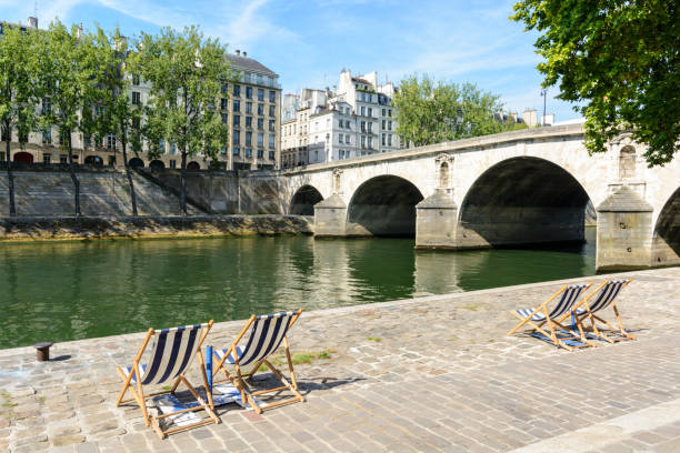 Deck chairs in the sun on the bank of the river Seine Blue and white striped deck chairs in the sun on the bank of the river Seine with typical parisian bridge and buildings in the background. riverbank stock pictures, royalty-free photos & images