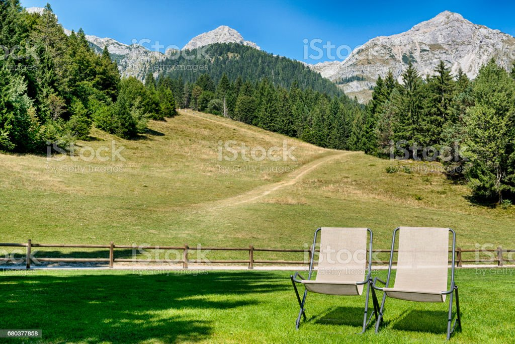 Deck chairs on the grass with mountains in the background stock photo