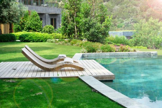 Liegestühle auf Holzplankenboden gegen Schwimmbad – Foto