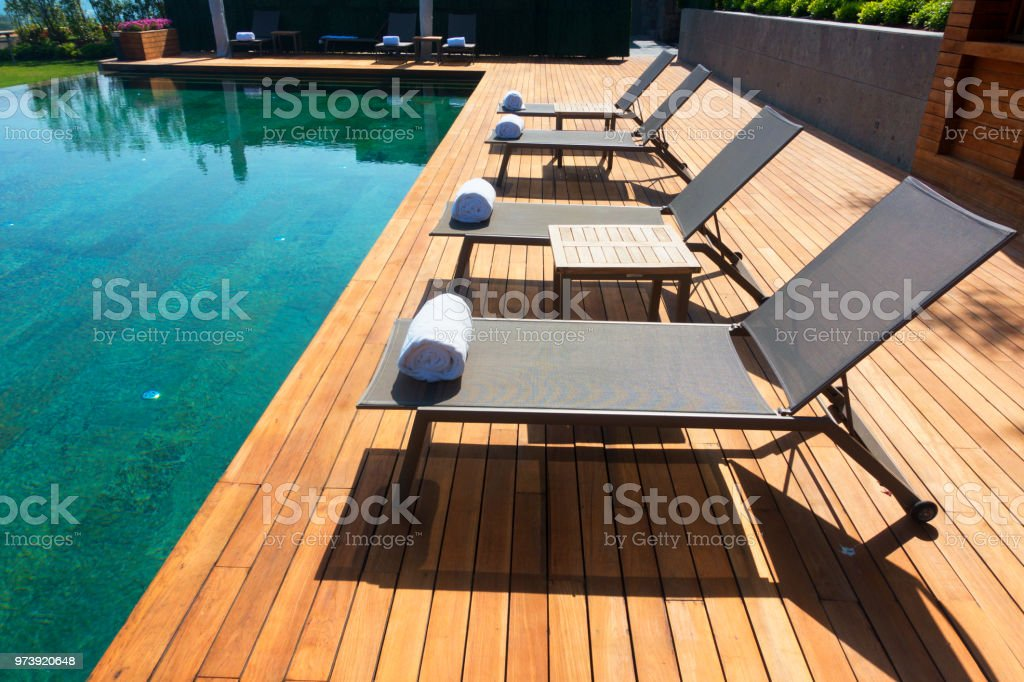 Deck Chairs On Wooden Plank Floor Against Swimming Pool ...